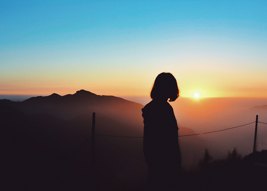 A woman watches the sunset.